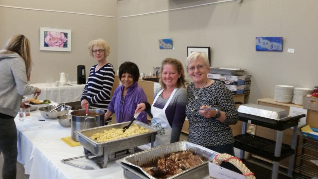 Volunteers serving a meal at St. Luke's Community Dinner
