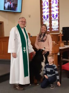The Rev. Hollis Hiscock with a St. Bernard and many other pets.