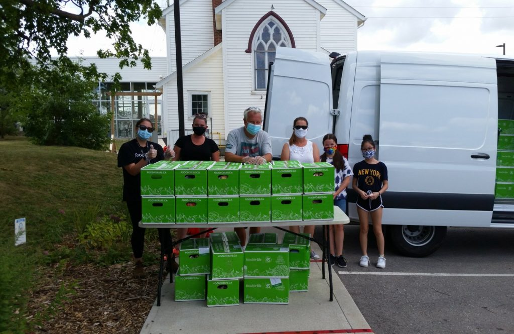 Food for Life Volunteers prepare to hand out Summer Fun Boxes outside St. Luke's