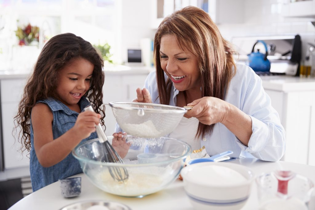 Young Hispanic girl making cake in the kitchen with her grandma, close up